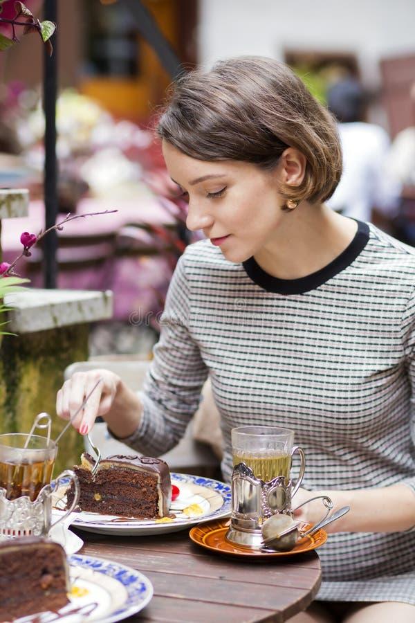 咖啡馆套的妇女与叉子的蛋糕 免版税库存图片