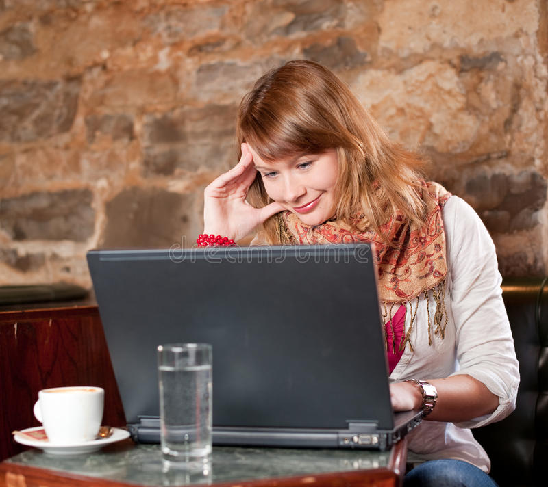 咖啡馆女孩互联网膝上型计算机运作的年轻人 免版税库存图片