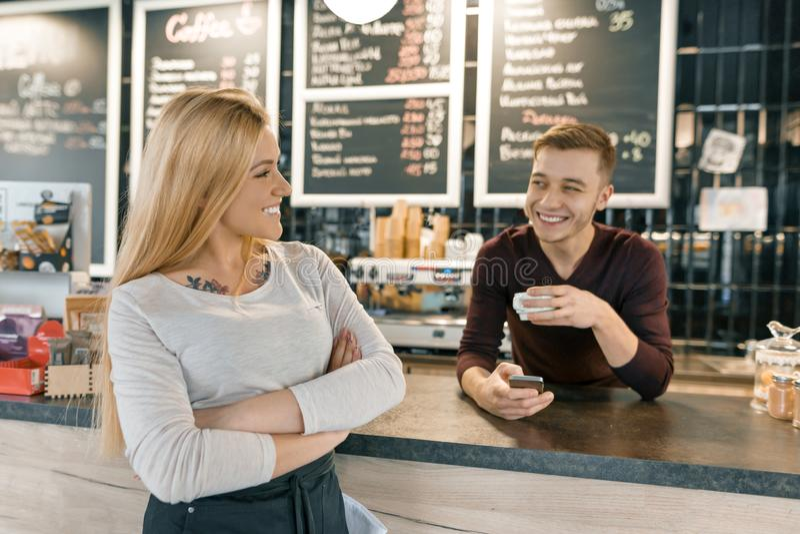咖啡馆工作者、男人和妇女年轻微笑的夫妇摆在酒吧柜台和咖啡机附近的有杯子的新鲜的咖啡 库存照片