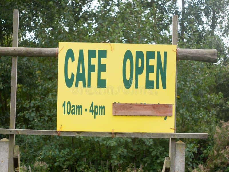 咖啡馆开放10am-4pm的黄色标志关闭 免版税库存图片