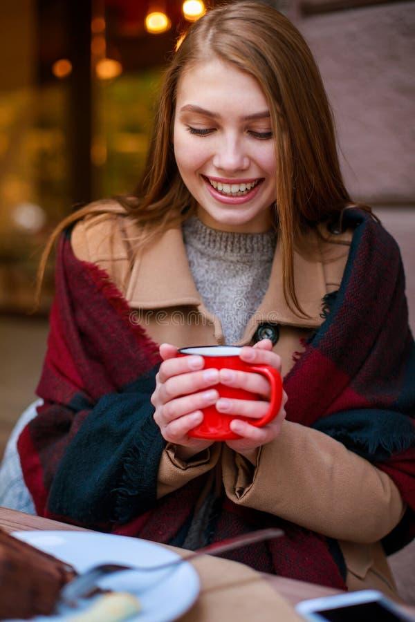 咖啡馆的一个女孩拿着有饮料的一个杯子 库存图片