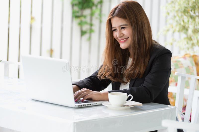 咖啡馆的亚洲年轻女商人 免版税库存照片