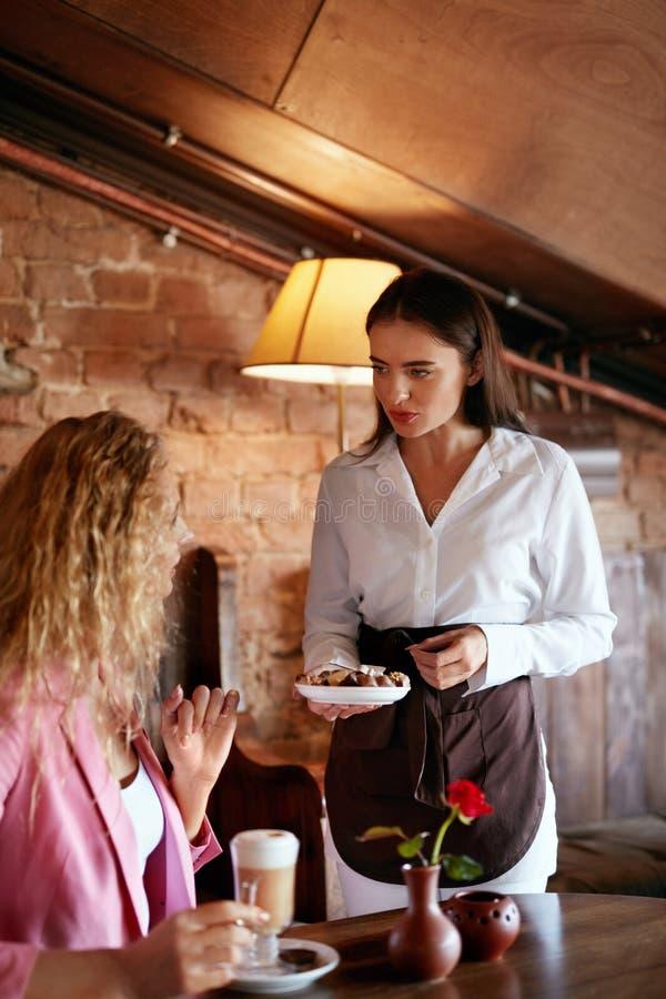 咖啡馆的人们 服务女性客户的女服务员 免版税库存图片