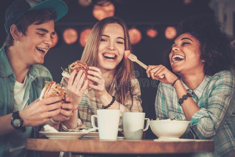 咖啡馆的多种族朋友 免版税库存照片