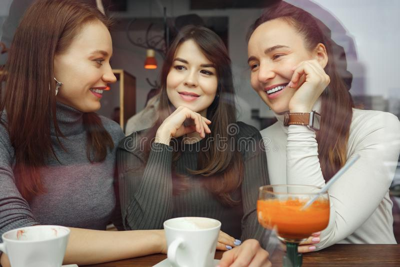 咖啡馆的妇女女朋友获得一个乐趣聊天和喝他们的饮料的 看法从后面玻璃 图库摄影