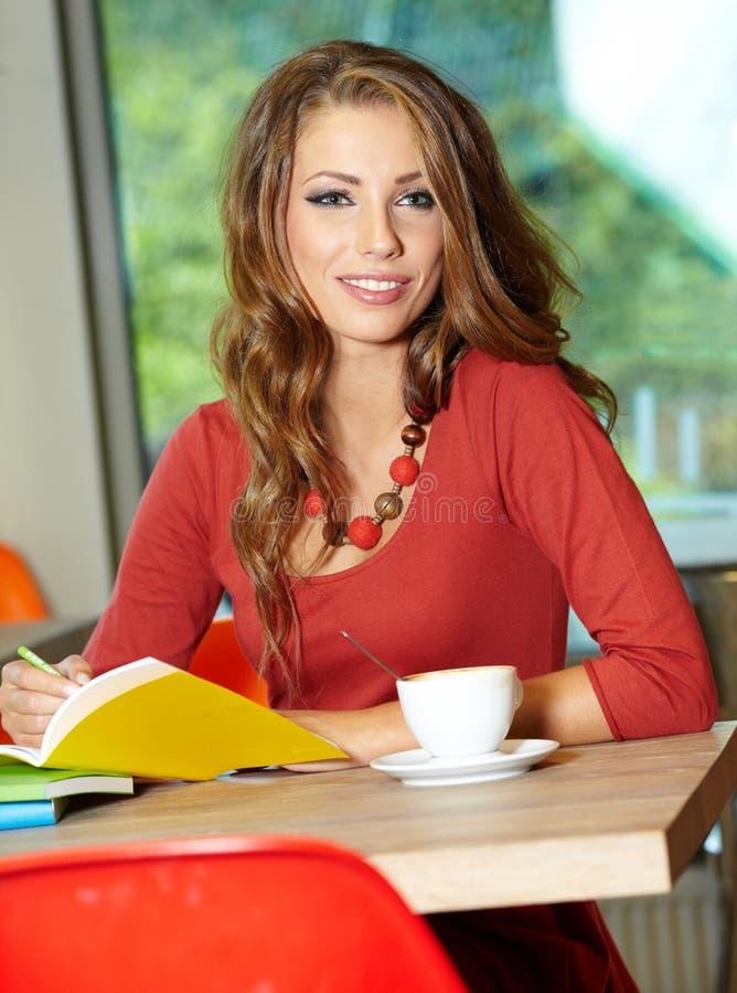 咖啡馆的学员女孩 免版税库存照片