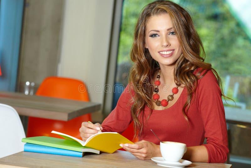 咖啡馆的学员女孩 免版税库存图片