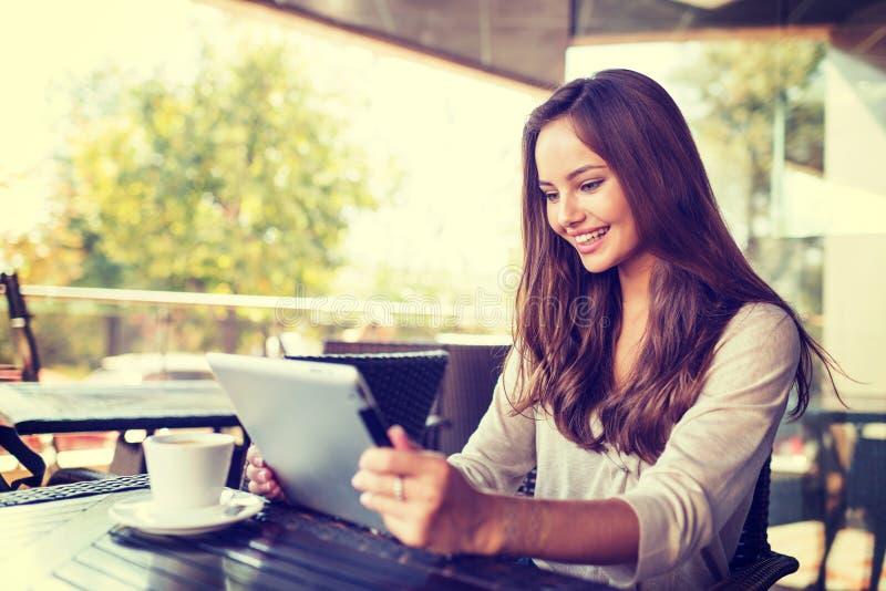 咖啡馆的少妇使用片剂 免版税库存照片