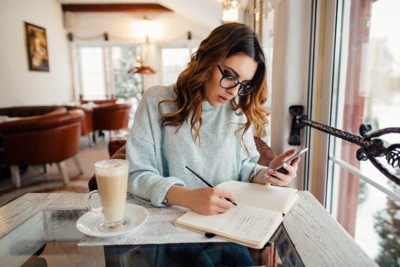 咖啡馆的年轻女商人在笔记本写笔记 免版税图库摄影