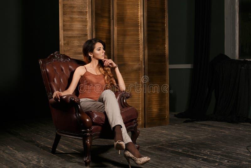 咖啡馆的沉思美丽的少妇看窗口 扶手椅子的画象相当女孩在现代公寓在早晨 免版税库存图片