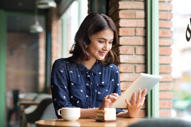 咖啡馆的美丽的逗人喜爱的亚裔年轻女实业家,使用digi 免版税库存图片