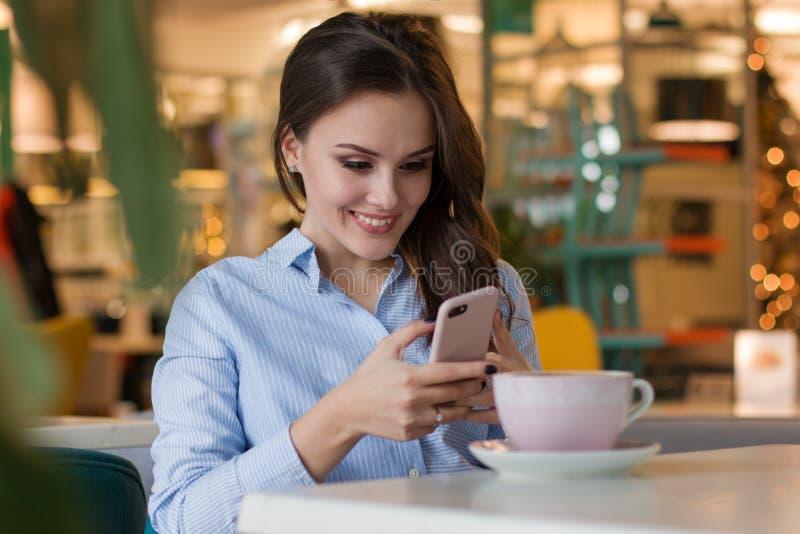 咖啡馆的美丽的逗人喜爱的白种人少妇,使用手机和饮用的咖啡微笑 免版税库存图片