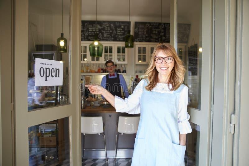 咖啡馆等待她的客人的店主女实业家,当年轻barista身分在背景中时 库存图片