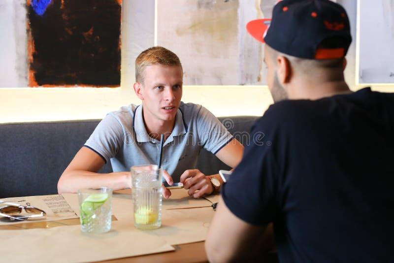 咖啡馆谈话的男性朋友与技术电话片剂谈论 免版税库存图片