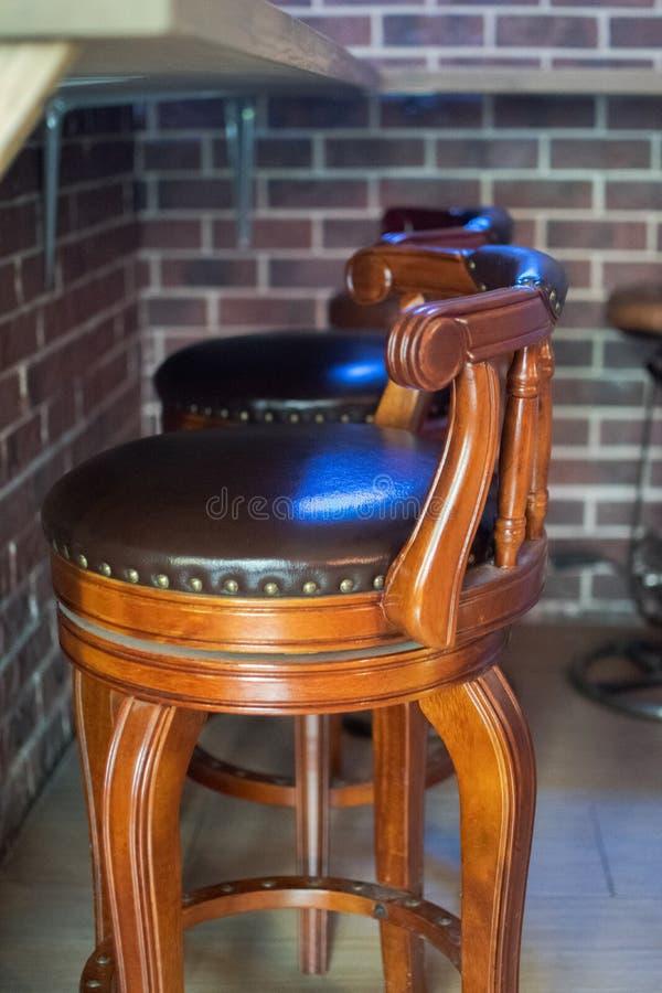 咖啡馆酒吧内部-木酒吧和酒吧椅子 在木酒吧柜台附近的布朗皮椅 库存图片