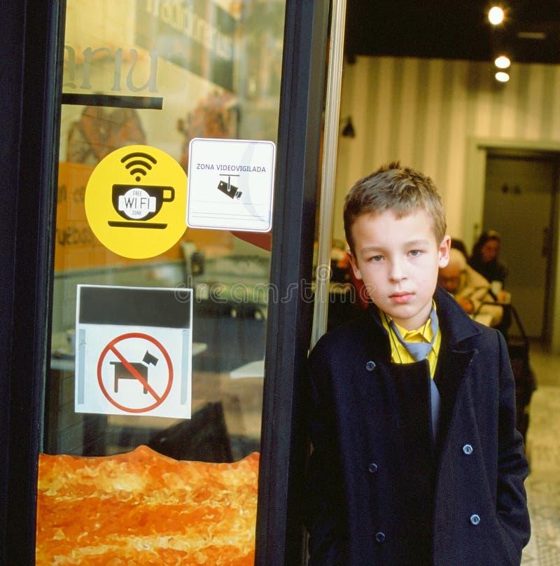 咖啡馆门道入口的学童 免版税库存图片