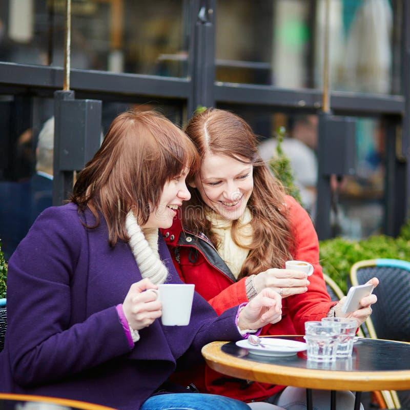 咖啡馆饮用的咖啡和使用的手机两个女孩在巴黎,法国 免版税库存照片
