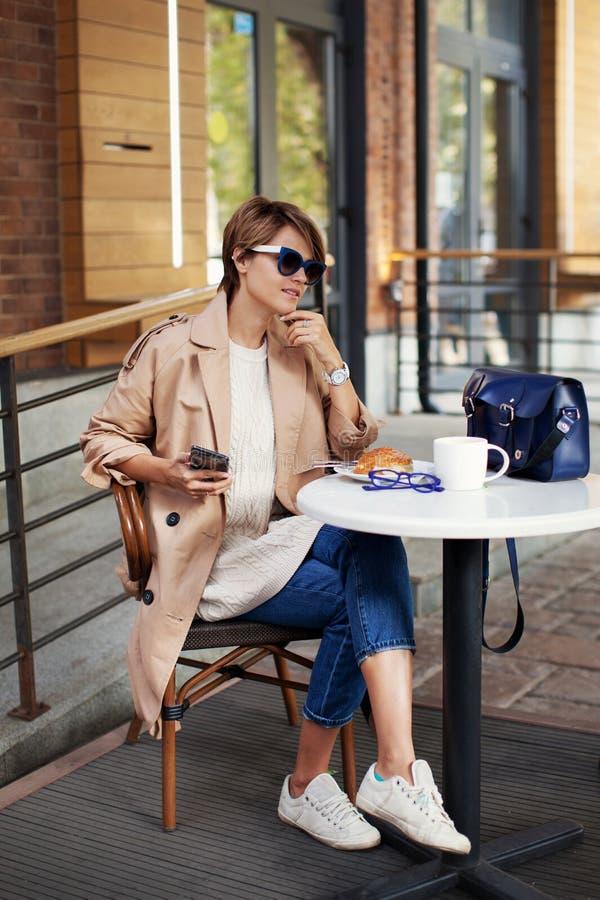咖啡馆饮用的咖啡和吃新月形面包的美丽的性感的妇女 佩带的样式时兴的春天或秋天给米黄沟槽穿衣 库存照片