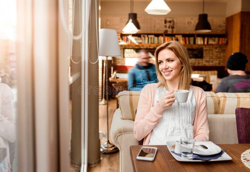 咖啡馆饮用的咖啡的妇女,享用她的浓咖啡 免版税库存图片