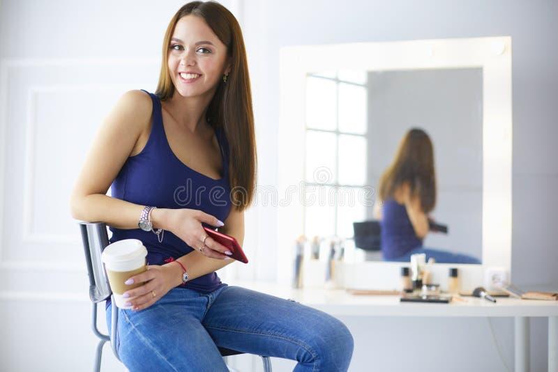 咖啡馆饮用的咖啡的年轻女人和谈话在手机 库存照片