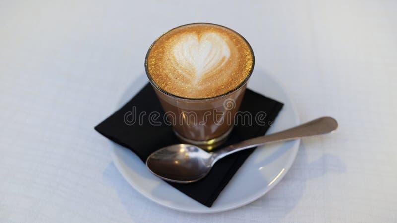 咖啡馆cortado,在与心形的泡沫拿铁艺术的透明玻璃供食的一份传统西班牙咖啡在上面 图库摄影