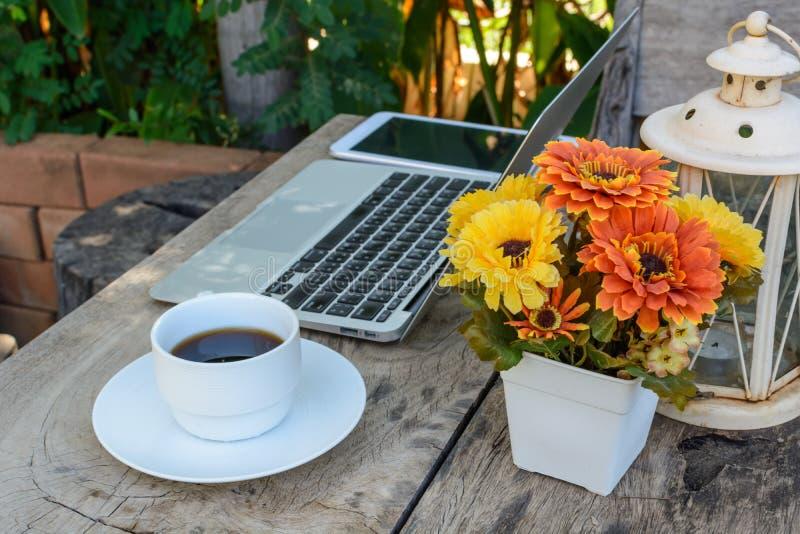 咖啡,在木地板上的膝上型计算机与花 免版税库存照片