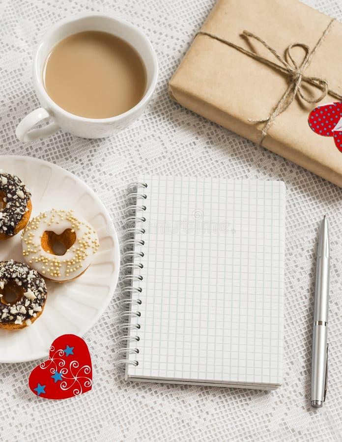 咖啡,油炸圈饼,自创情人节礼物,红色纸心脏,空白开放笔记本 免版税库存照片