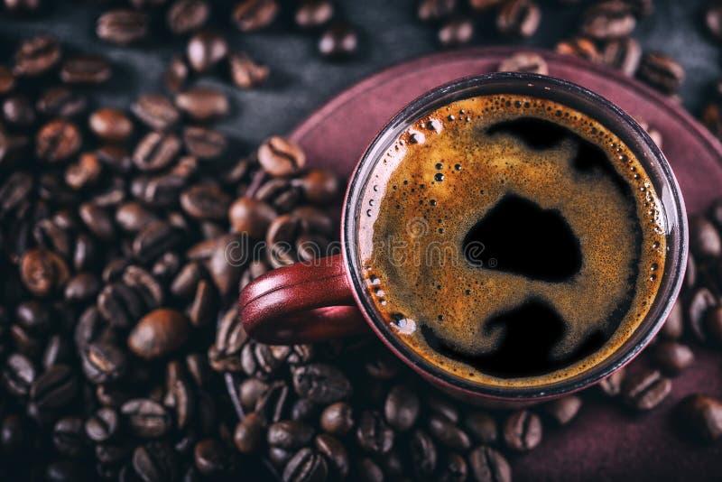咖啡 杯无奶咖啡和溢出的咖啡豆 背景中断咖啡新月形面包杯子甜点 免版税库存照片