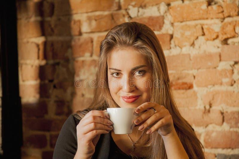 咖啡 美丽的在咖啡馆的女孩饮用的咖啡 秀丽式样Wom 免版税库存图片