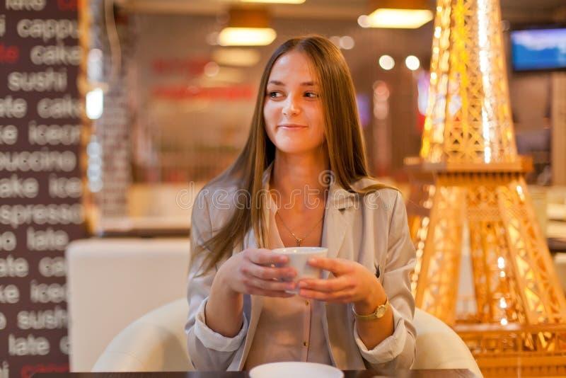 咖啡 美丽的女孩饮用的茶或咖啡在咖啡馆 免版税库存图片
