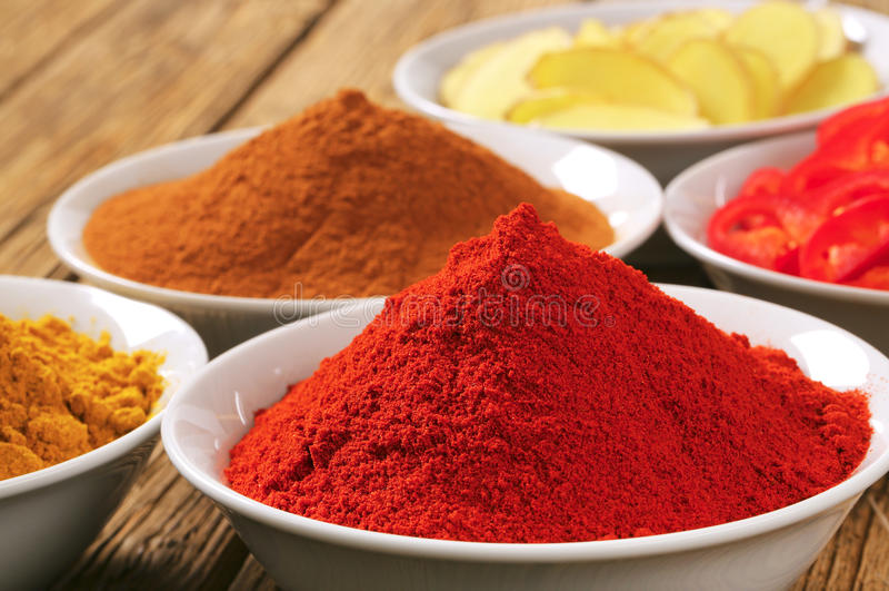 咖喱粉,辣椒粉,肉桂粉,被切的姜根和 免版税库存照片