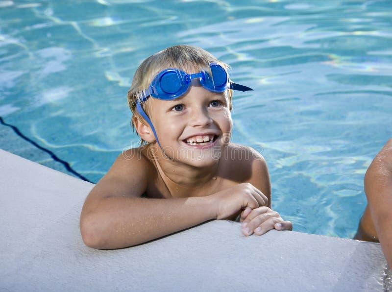 咧嘴停止的池副游泳的男孩 免版税库存图片