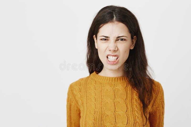 咧嘴和斜眼看在照相机的被激怒的疯狂的欧洲妇女特写镜头画象,表达愤怒和身分  免版税库存图片