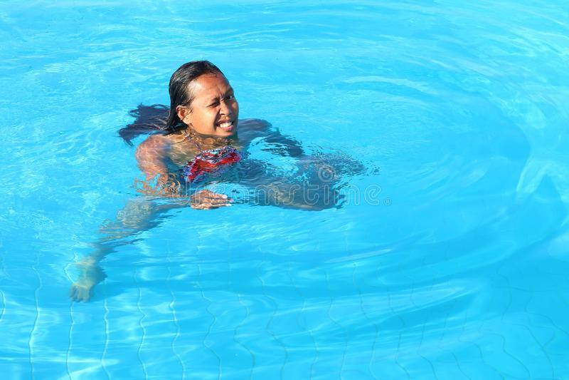 咧嘴游泳在水池的妇女 库存图片