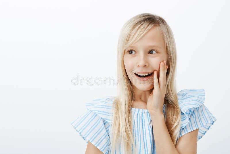 咧嘴笑的愉快的矮小的白种人女孩画象有长的公平的头发的,看在旁边与纯净的快乐的微笑,举行 图库摄影