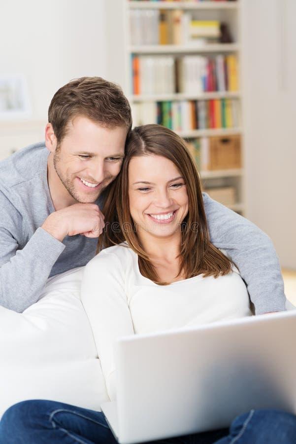 咧嘴在膝上型计算机的内容的年轻夫妇 免版税库存照片