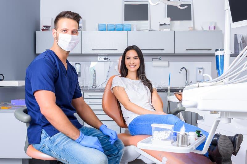 咨询一名女性患者的一位年轻牙医在牙齿演播室 库存照片
