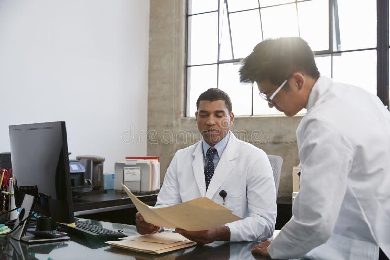 咨询的两位男性医生在书桌在办公室 图库摄影