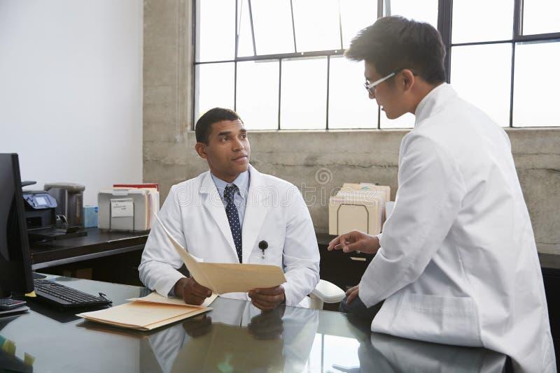 咨询的两位男性医生在书桌在办公室 库存图片