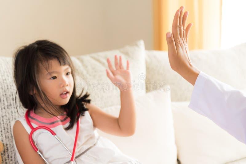咨询的愉快的矮小的逗人喜爱的女孩在儿科医生 免版税库存照片