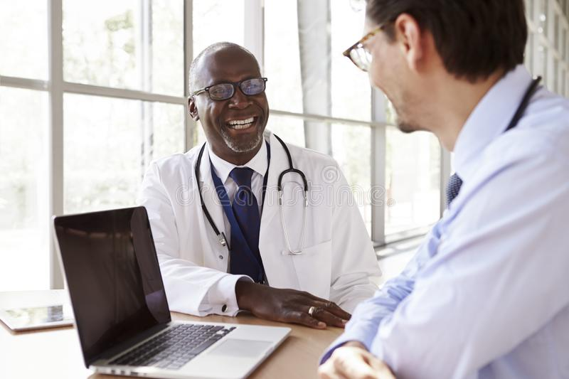 咨询笑的两名资深医疗保健工作者 免版税库存照片