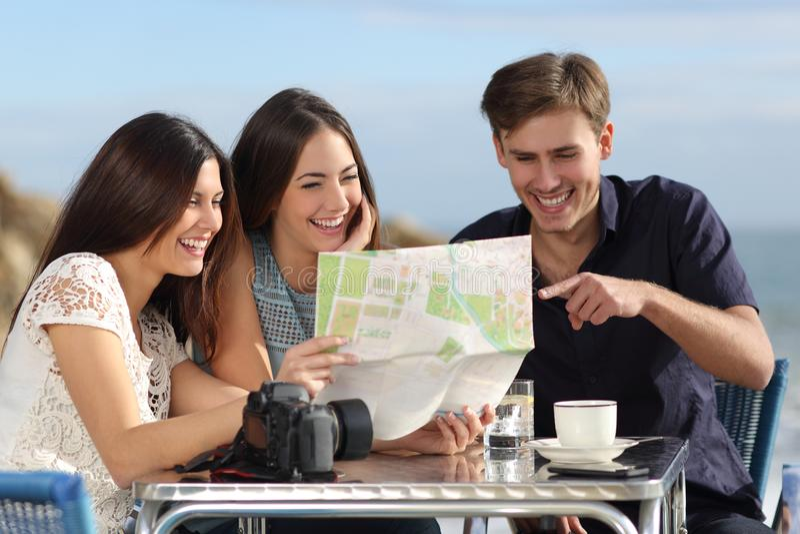 咨询纸地图的小组年轻旅游朋友 免版税库存图片