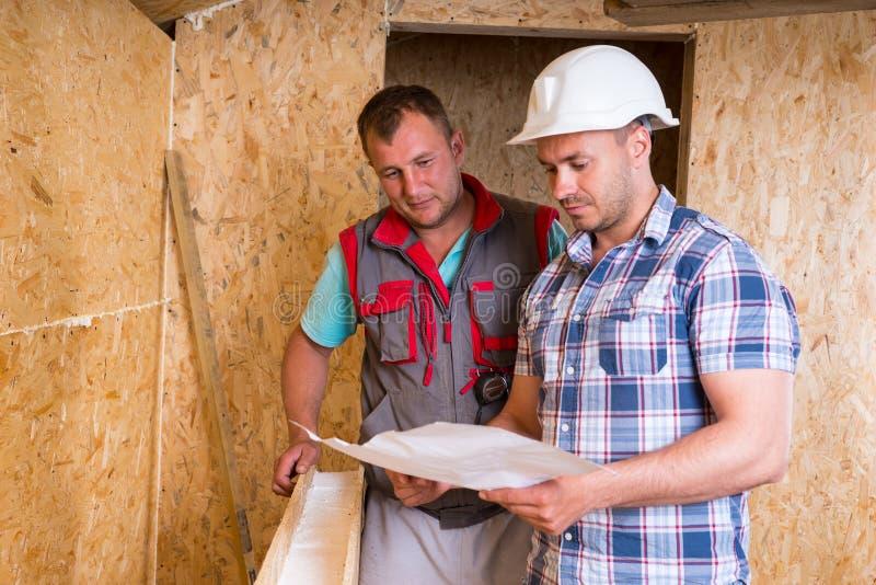 咨询计划的建筑工人在新的家 库存照片