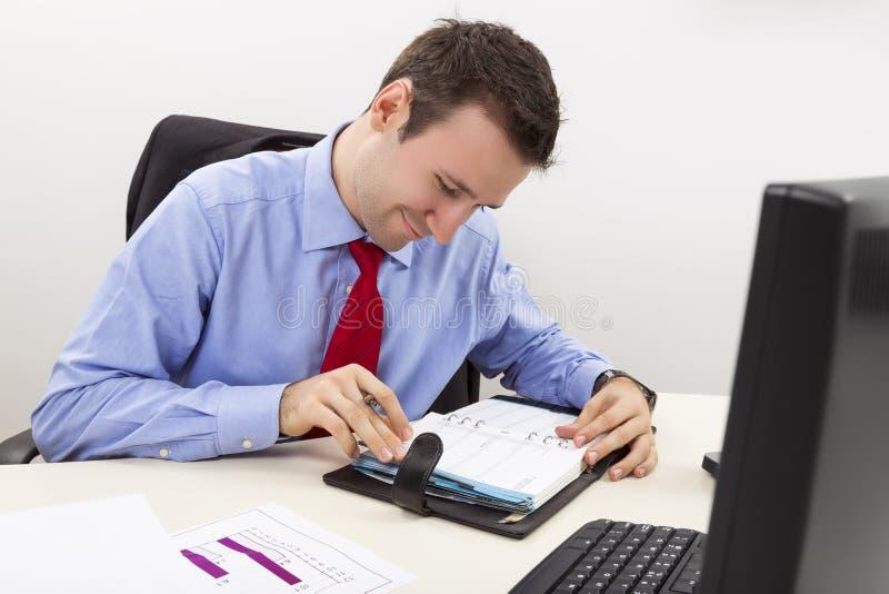 咨询他的议程的愉快的企业家 免版税图库摄影