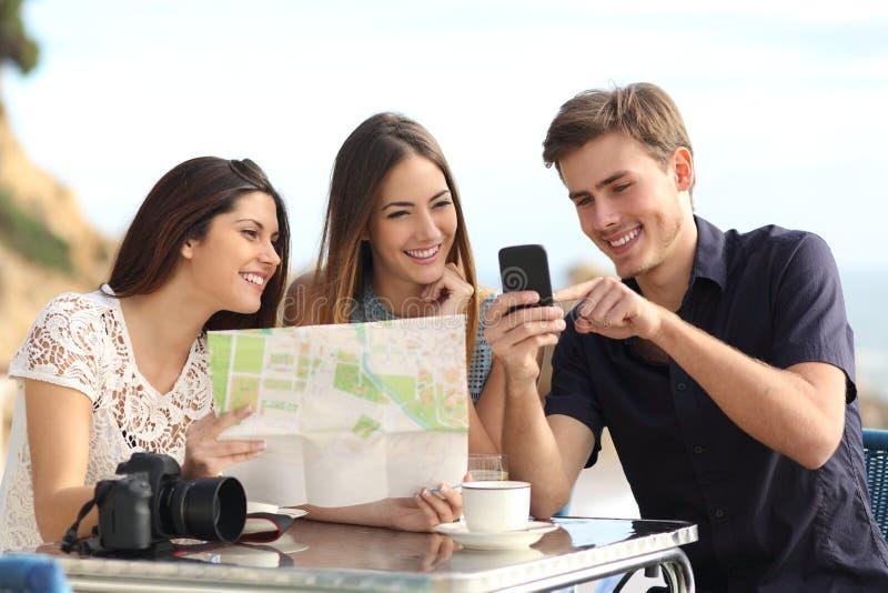 咨询gps的小组年轻旅游朋友在一个巧妙的电话映射 免版税图库摄影