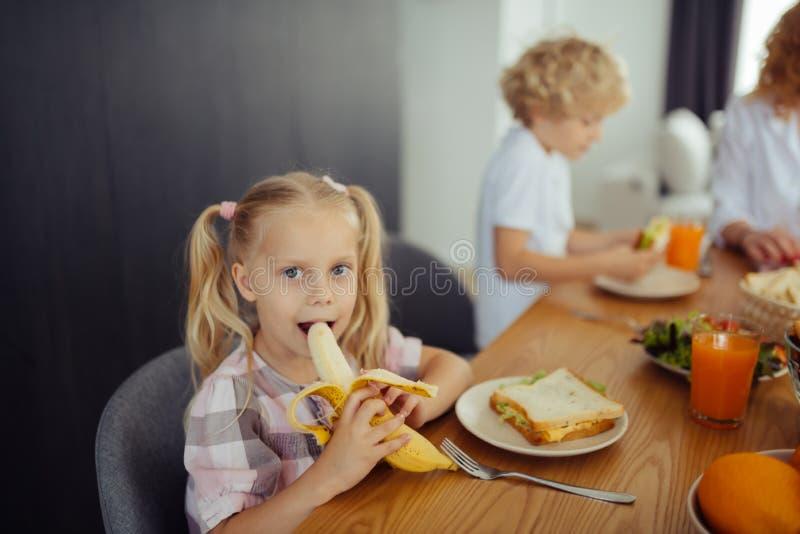 咬住一个可口香蕉的愉快的正面女孩 免版税库存图片