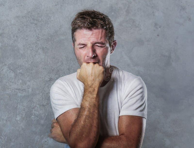 咬住他的拳头绝望感觉的哀伤和沮丧的人被挫败和无能为力在消沉和悲伤表情concep 免版税库存图片