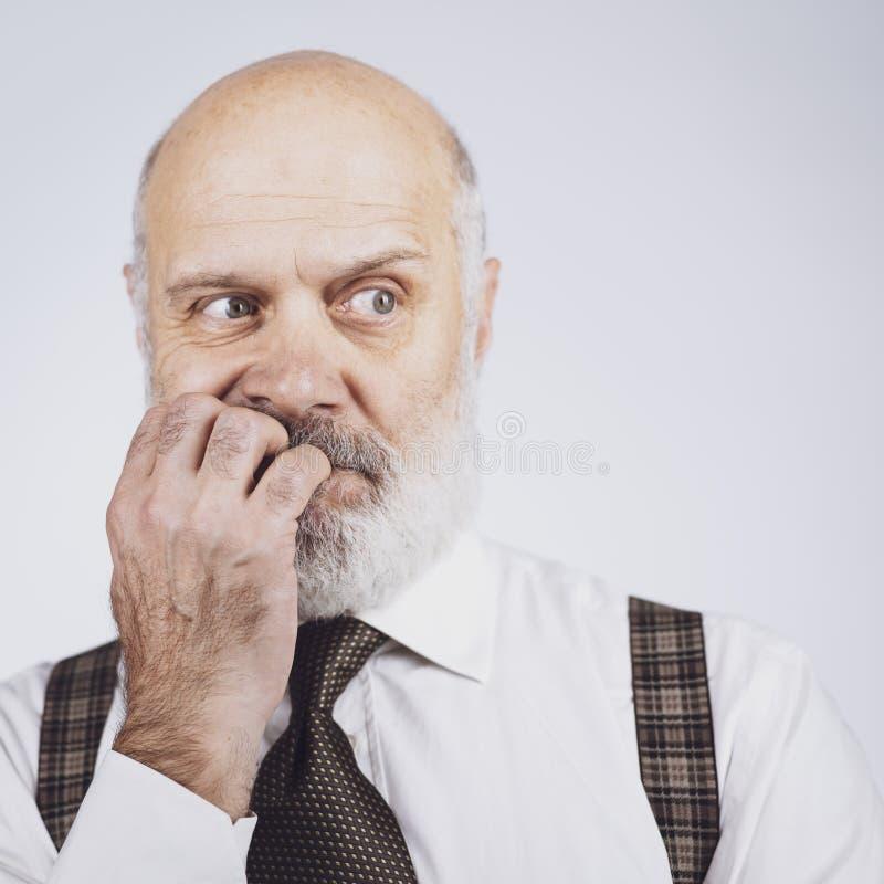 咬住他的钉子的紧张的急切老人 免版税库存照片