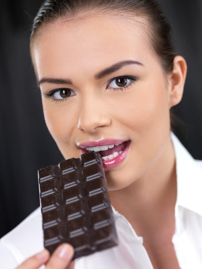 咬住入巧克力的可爱的妇女 免版税库存图片