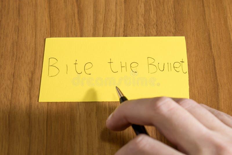 咬住在一张黄色纸的子弹handwrite与在tabl的一支笔 图库摄影
